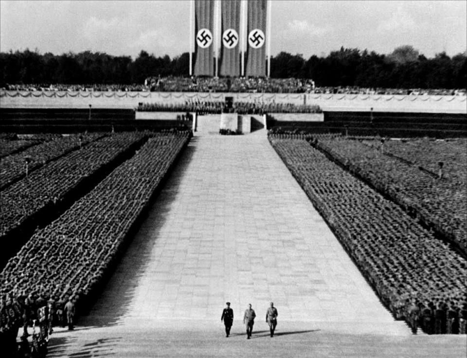 El triunfo de la voluntad (película propagandista nazi), dirigida por Leni Riefenstahl, (1935). Las técnicas utilizadas por Riefenstahl, que incluyeron cámaras en movimiento, el uso de teleobjetivos para crear una perspectiva distorsionada, fotografía aérea y un revolucionario enfoque en el uso de la música y la cinematografía, han hecho que El triunfo de la voluntad sea considerado como el documental político artístico mejor consumado en la historia del cine.
