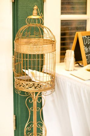 golden birdcage holds cards from guests @myweddingdotcom