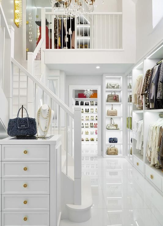 Luxurious 2 story walk-in closet showcases a tall white jewelry dresser placed against an all white staircase.