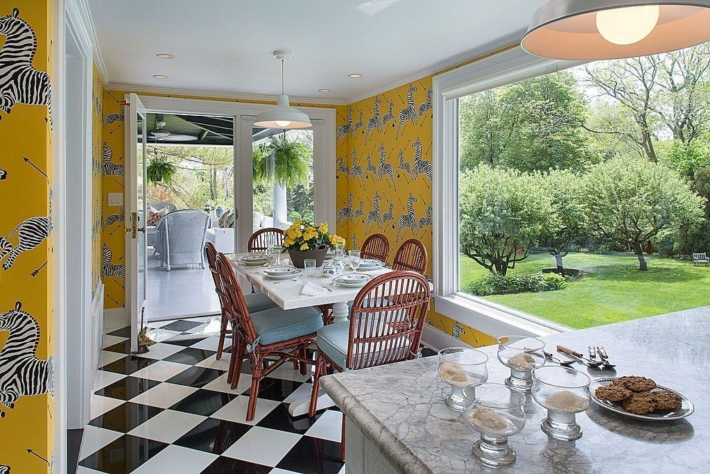 Dinette by Albert Hadley is full of color and pattern with white and black checkered tile flooring and vivid yellow zebra print wallpaper.