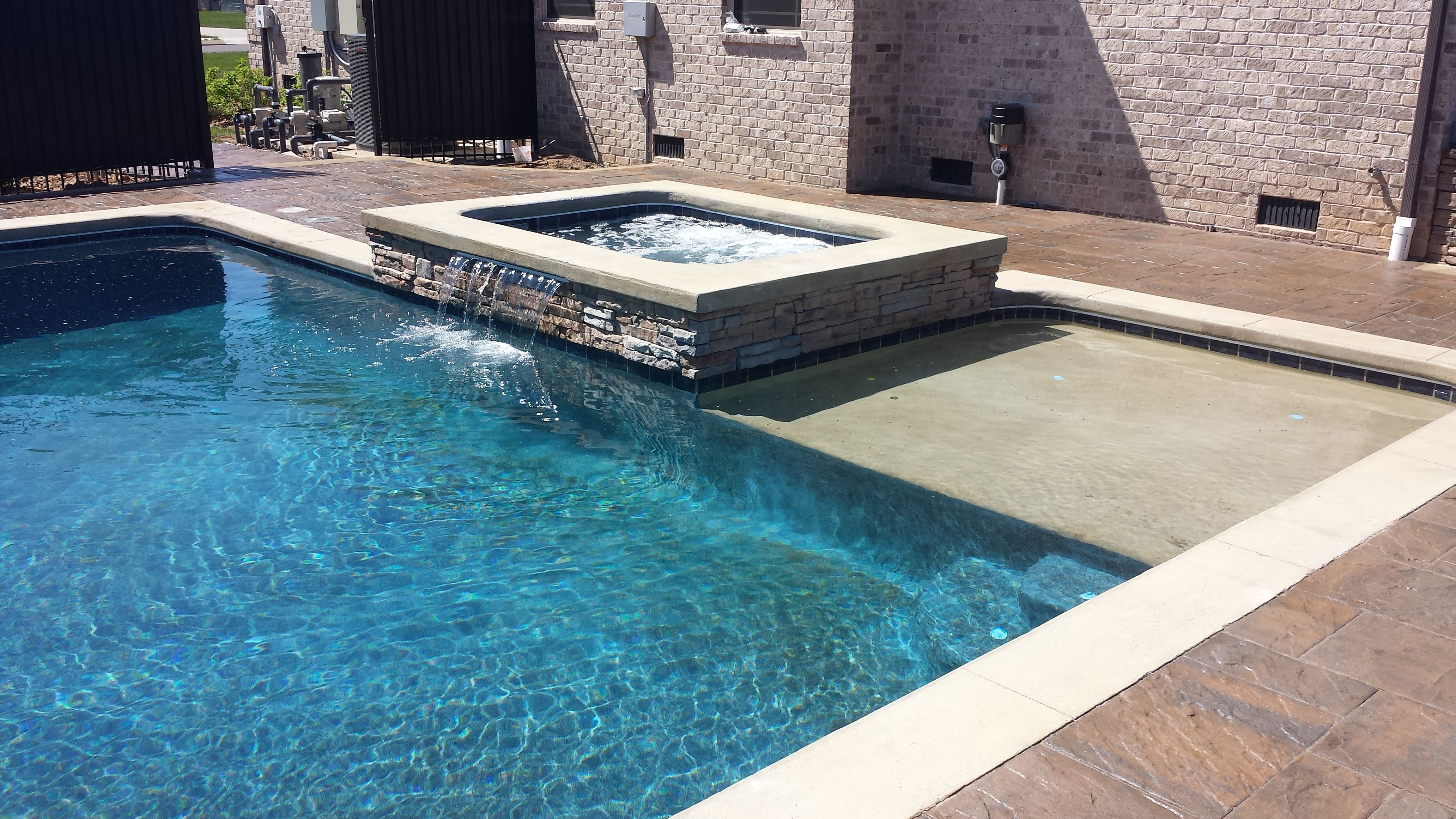 This pool features a sand color tanning ledge and a