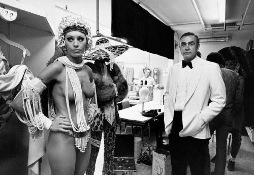"""Sean Connery on the set of Diamonds Are Forever.  """"Film sets can be short bursts of activity and long periods of boredom. Filming Diamonds Are Forever in Vegas, Sean liked to slip away and play the slots. And pose with the girls, of course.  """"At [notorious hotel/casino] Circus Circus — they all wanted to be photographed with Bond. And on the set of a Bond movie, there was only room for one ladies' man. Sean liked to be the girls' main focus."""" - Terry O'Neill"""