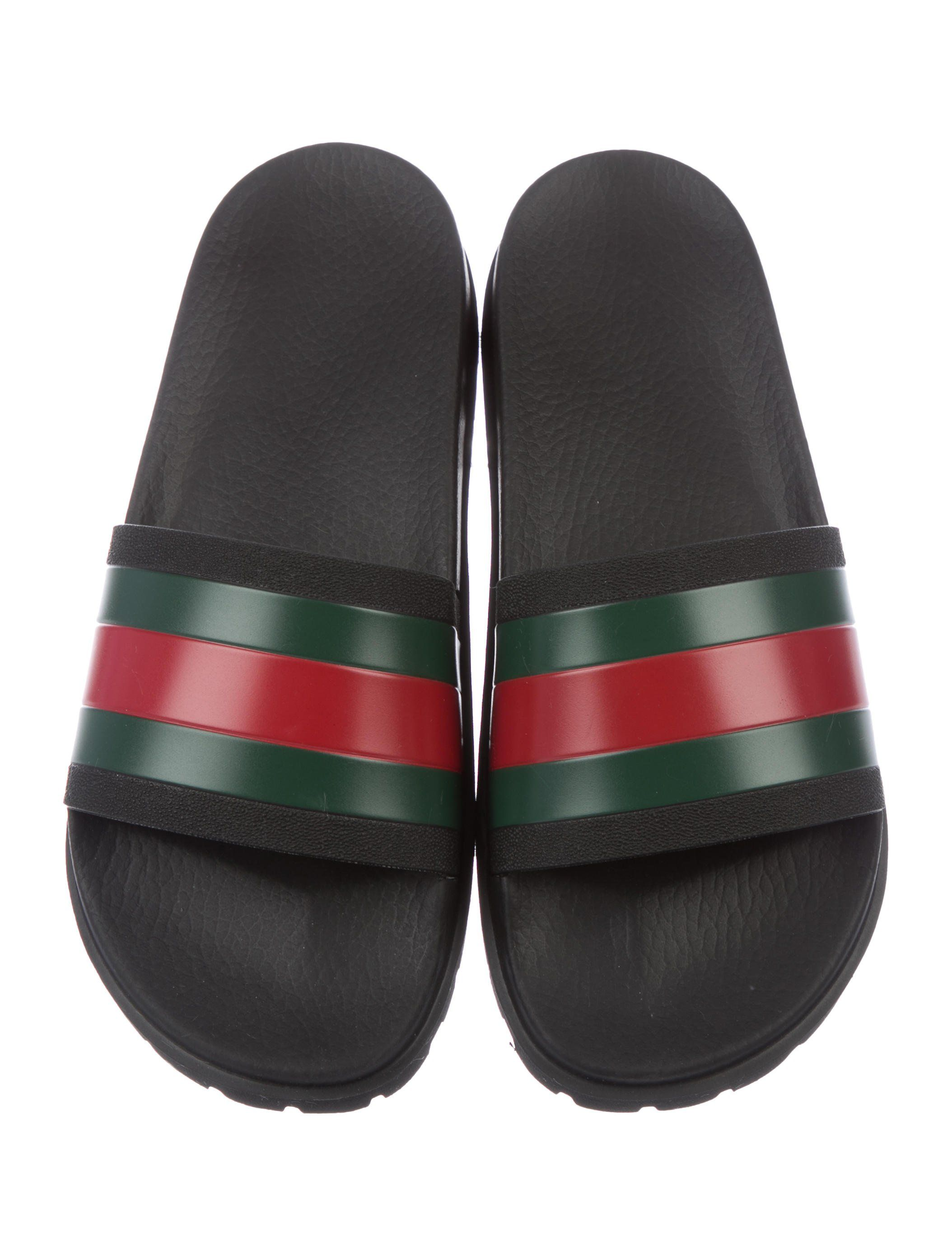 210bf4a77ad Black rubber Gucci slide sandals with red and green Web details at vamps  and rubber soles.