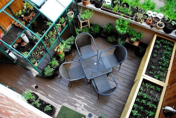 Photo of Balkon-Garten-mit-Topfpflanzen-üppiger-Vegetation-Holzdeck-grau-Tisch-und-gra …