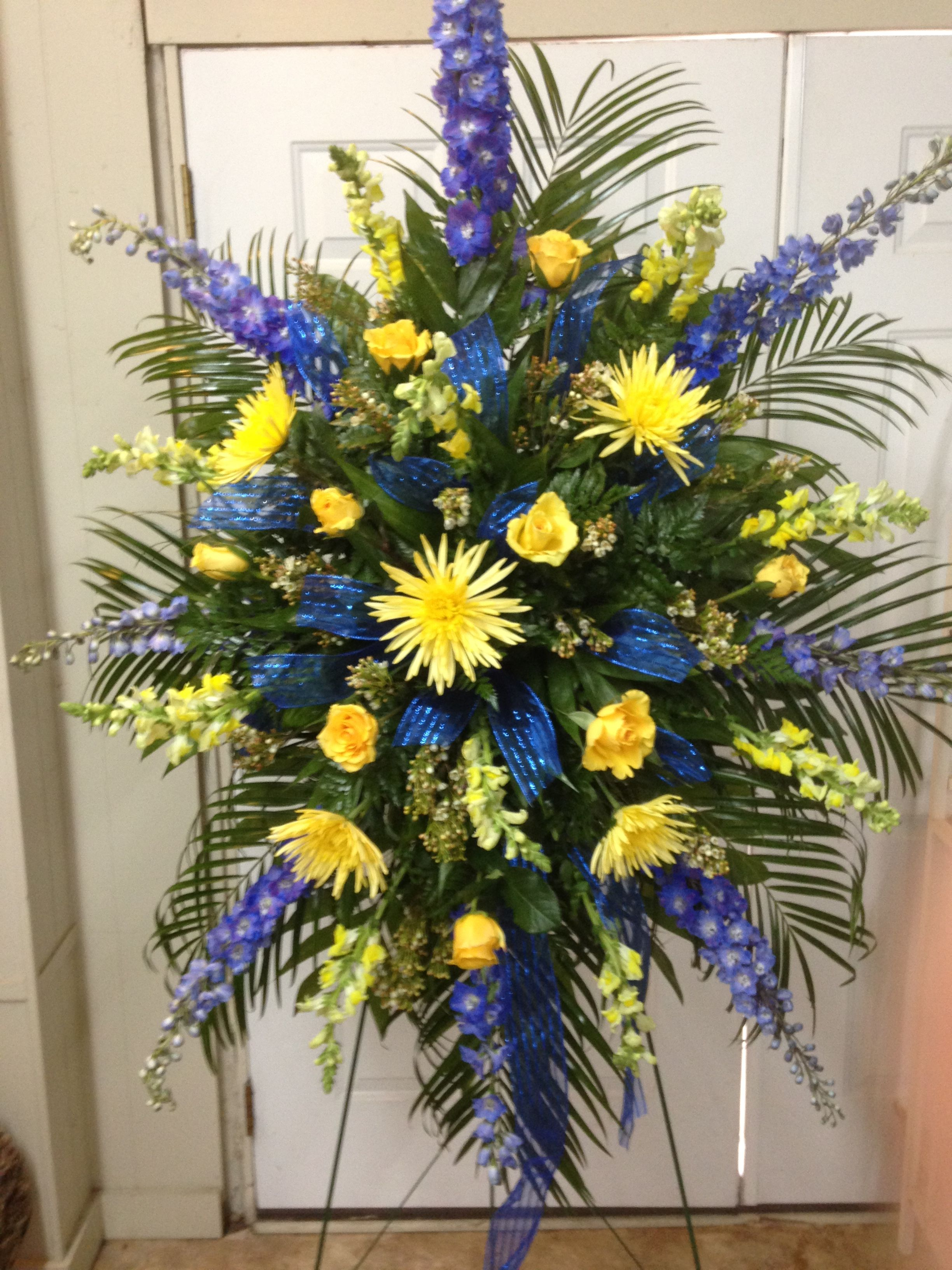 Fresh funeral spray using blue delphiniums yellow fuji