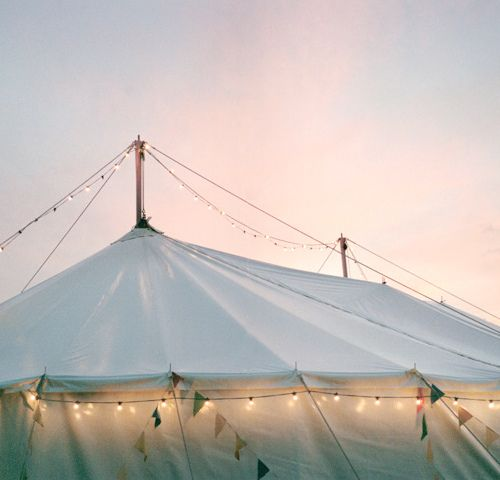 Lovely string lights surround an outdoor tent