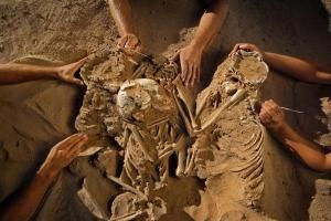 Stone Age embrace: A remarkable triple burial -- containing a woman and two children who were 5 (left) and 8 years old, their limbs entwined -- was discovered at the Gobero site during the 2006 field season. Pollen clusters found in the sand indicated the three had been buried on top of flowers. The skeletons showed no sign of injury and had been ceremonially posed and buried, along with four arrowheads. (Credit: Mike Hettwer (c) 2008 National Geographic)