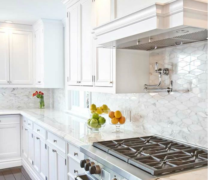 Chic White Kitchen Features White Cabinets Paired With Carrera