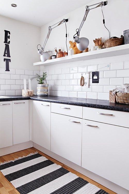 White kitchen, black countertop, wooden flooring, striped ...