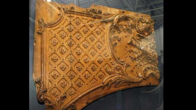 A Piece Of Wood From A Carved Archway Is Part Of A Display