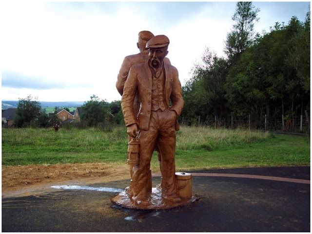 Two men carved from a fallen tree by chainsaw tree artist Tommy Craggs