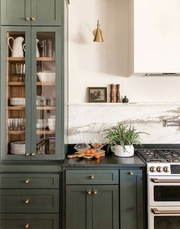 Photo of Green cabinets and brass hardware with soapstone counters.