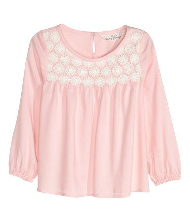 Long-sleeved blouse in airy woven fabric. Lace yoke, opening at back of neck with button, and elasticized cuffs.