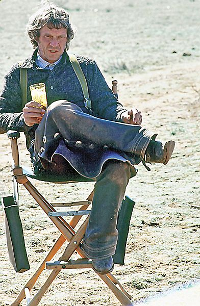 A leather-chapped McQueen sits in the director s chair on the set of Tom  Horn with a glass of iced down Old Milwaukee beer eda4f159a263