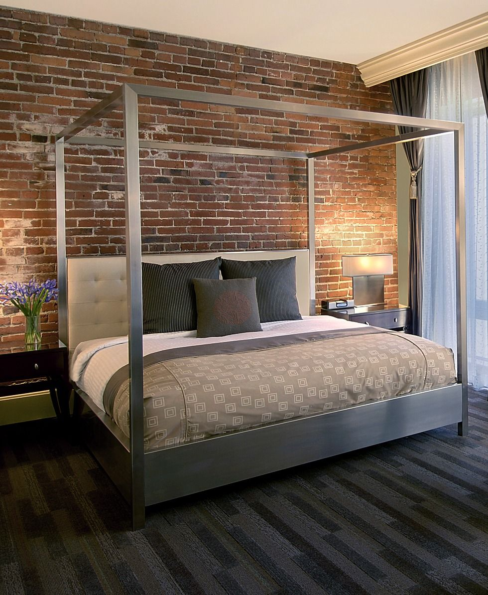 Urban bedroom decor: Metal canopy bed against red brick wall at ...