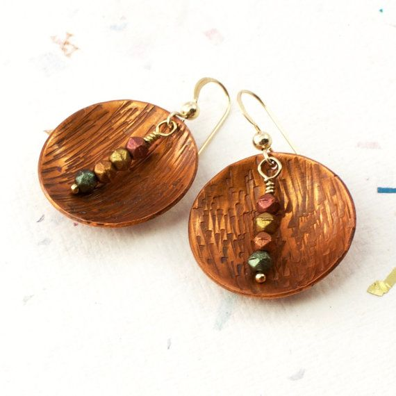 These textured copper earrings with patina feature handmade discs