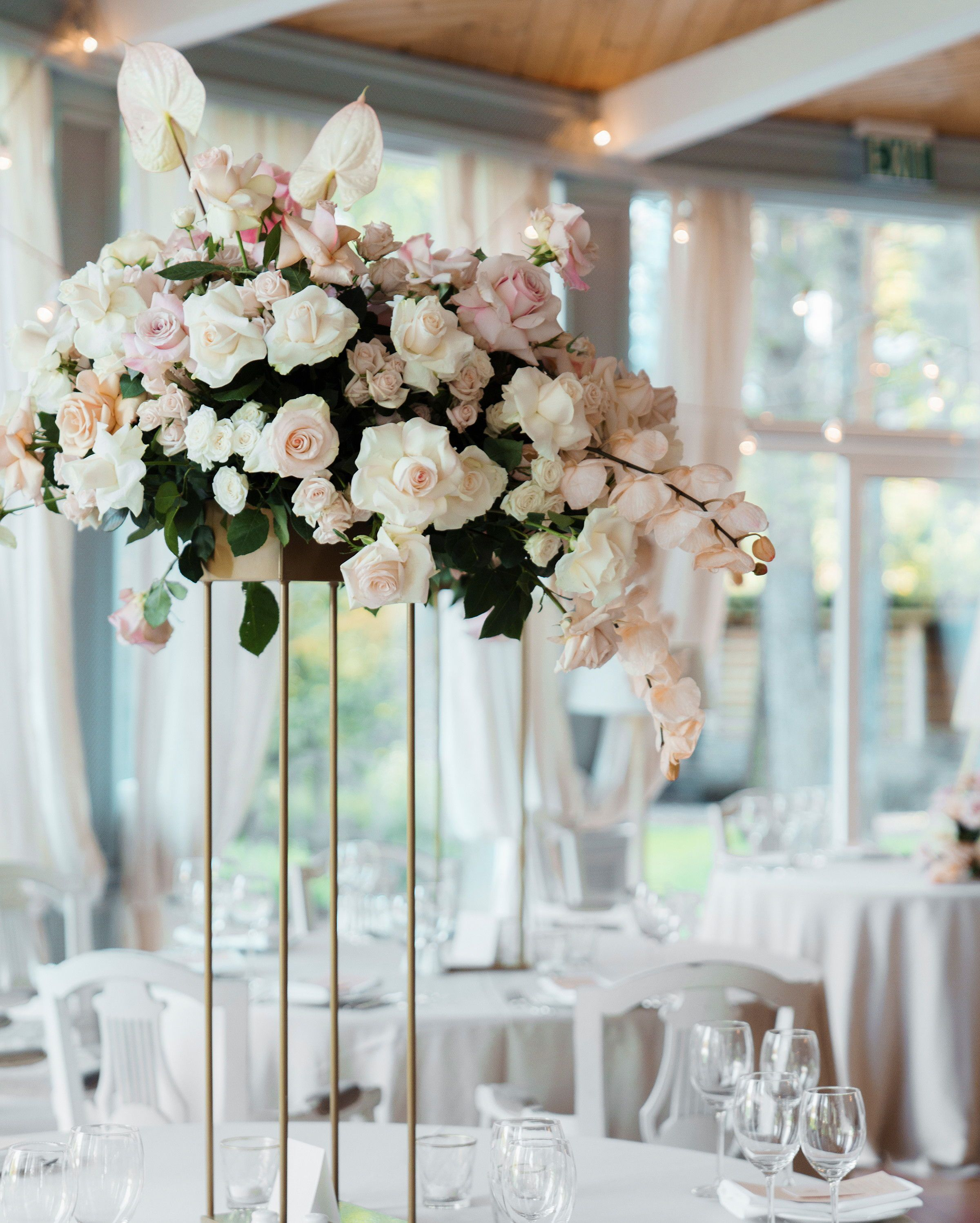 29 Tall Centerpieces That Will Take Your Reception Tables To New Heights Tall Wedding Centerpieces Wedding Reception Centerpieces Wedding Flower Arrangements