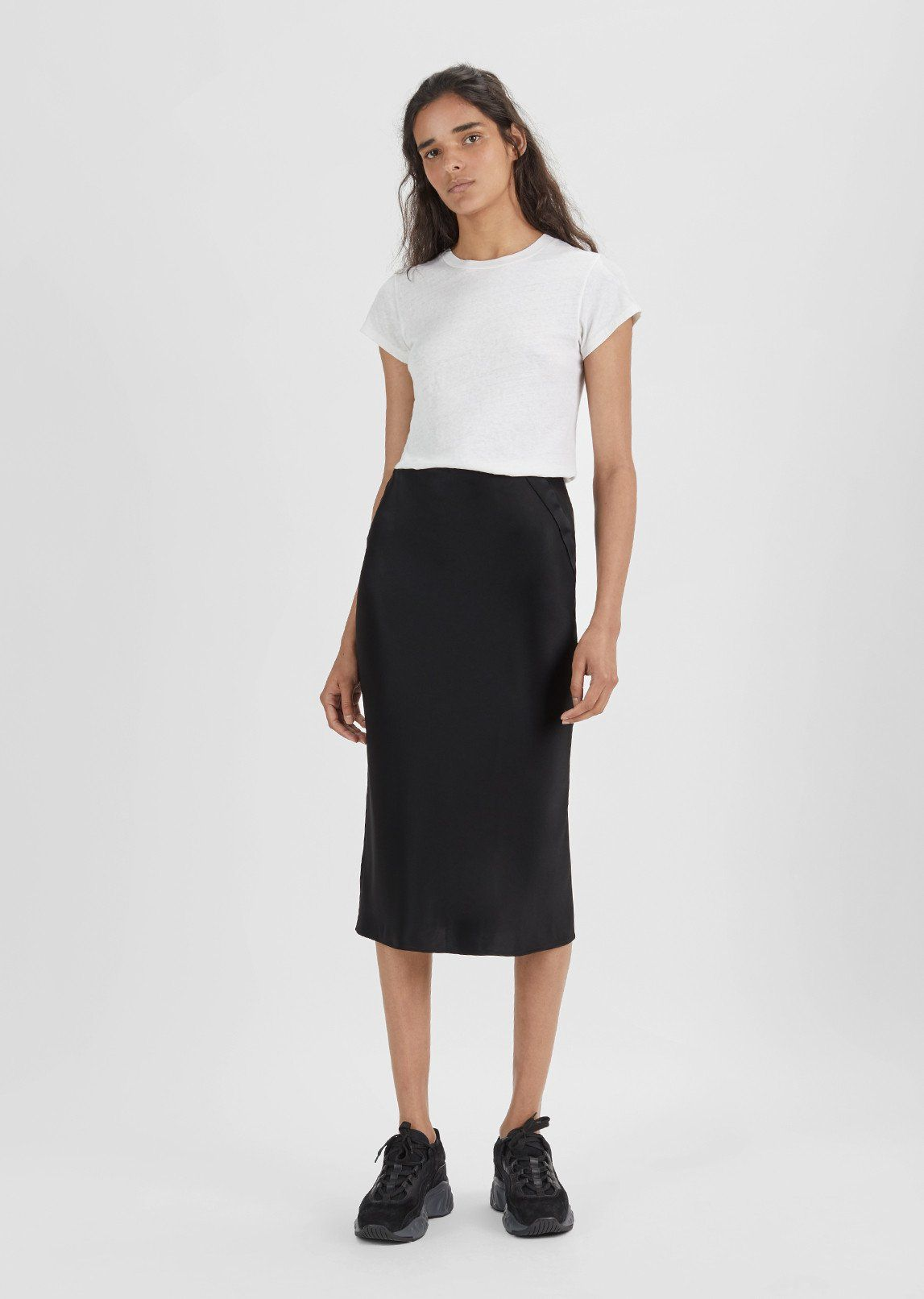 cb97b69c4 Black slim midi skirt with a curved side placket extends into a snap  closure for an adjustable back slit. Slim fit. Side zip closure. Color:  Black.