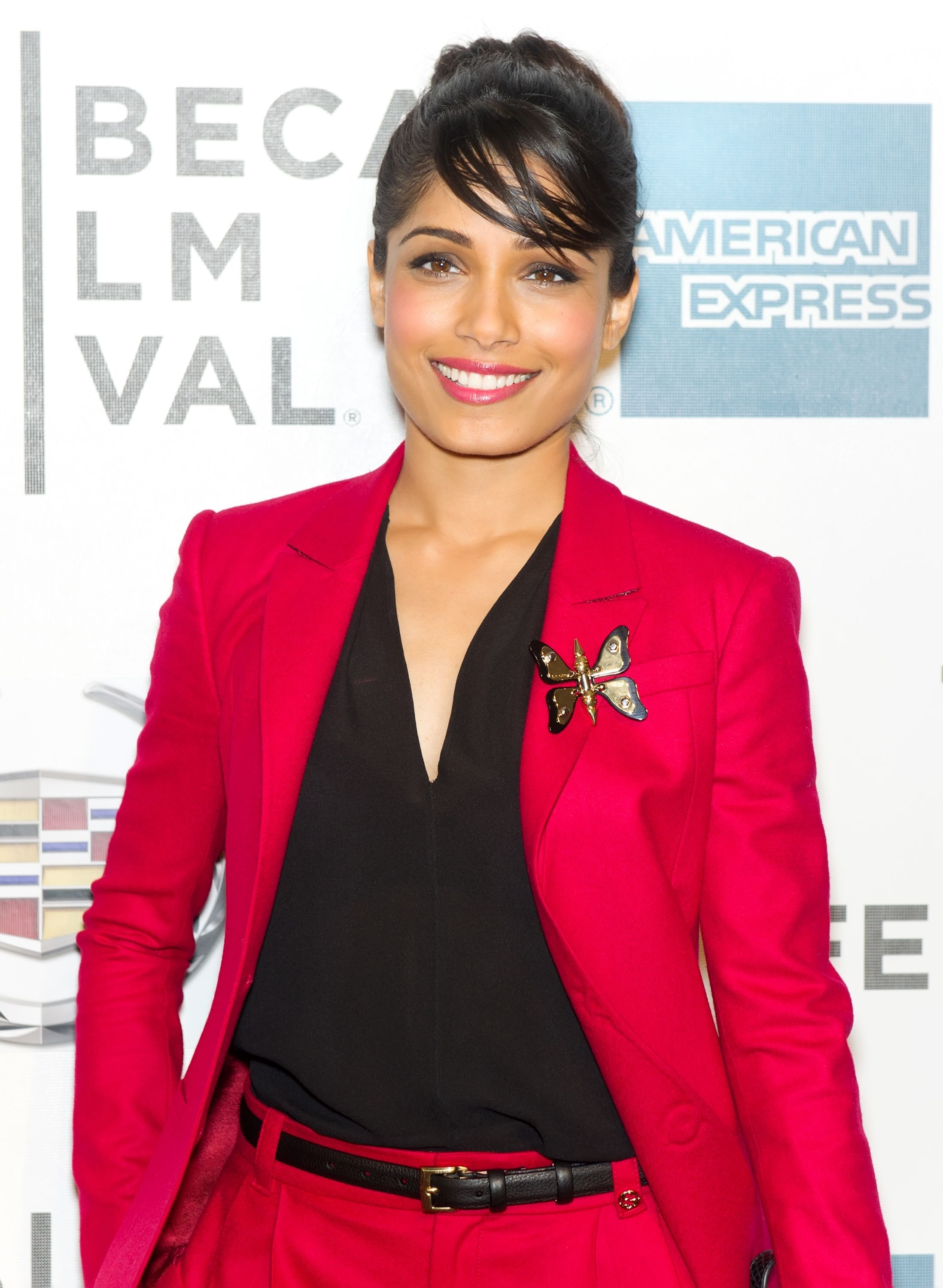 610dbc98fa5 Freida Pinto added a whimsical touch to her red Gucci suit with a black and  gold butterfly brooch.