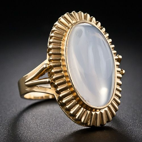 This chic, mid-century 10 Carat Moonstone Ring crafted in bright 18K Yellow Gold. The high Cabochon-cut Oval Moonstone shimmers from within a fluted textured frame. French assay and hallmarks on back of Ring Shank.  1,450 USD