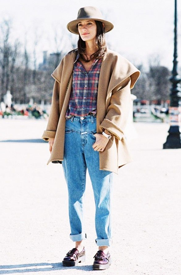A plaid shirt is worn with cuffed mom jeans, a camel wool coat, a felt hat, and platform loafers