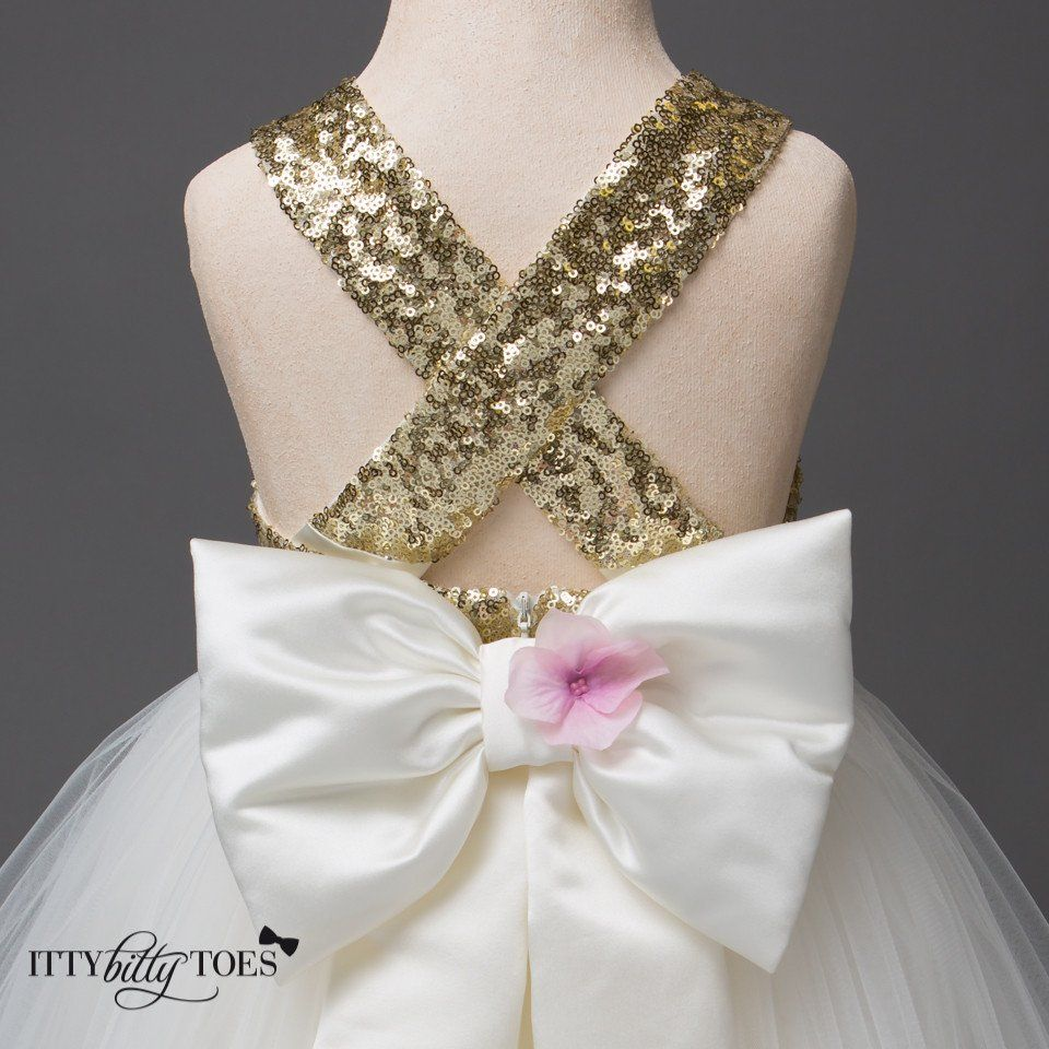 The perfect party dress for your little girl! Gold sequined bodice with a criss cross back top off six luxurious layers... Offered by Baby Boutique - Itty Bitty Toes!