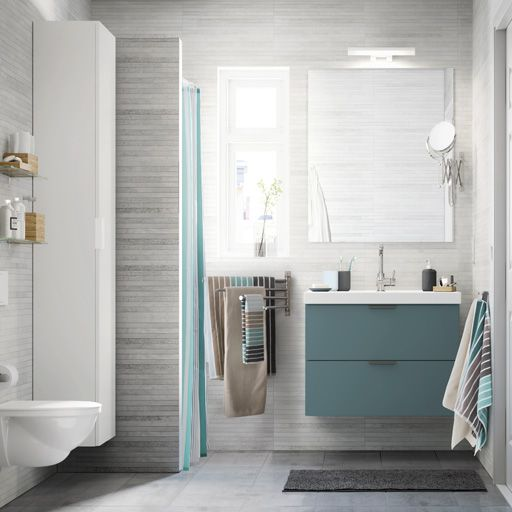A light grey small bathroom with a white high cabinet, a mirror and ...
