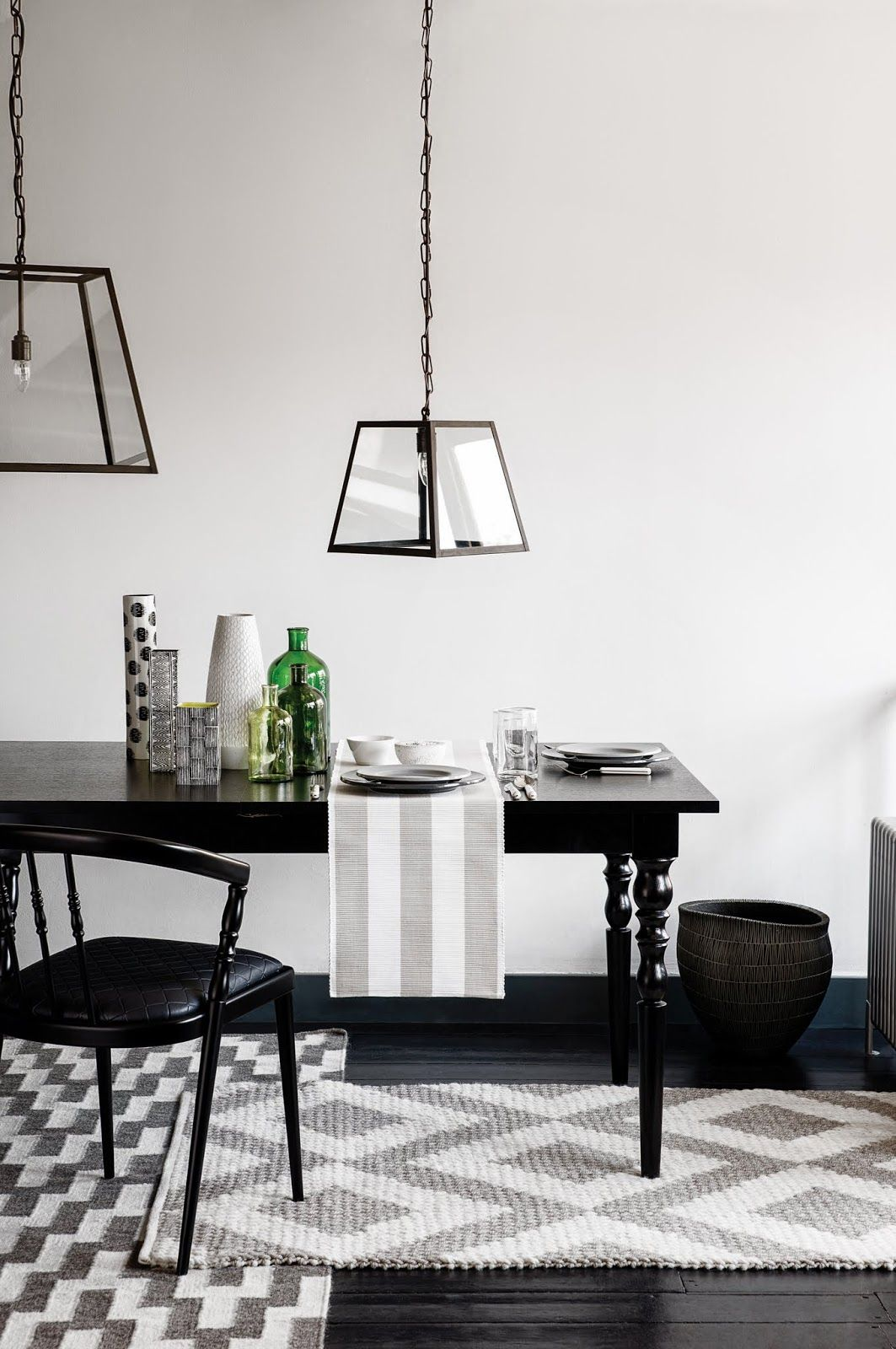 Wonderful overlapping gray rugs in this black and white dining room ...