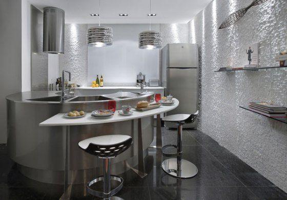 cozinha americana bastante funcional, as formas curvas acompanham o fluxo de pessoas, a geladeira está numa posição que tanto quem cozinha quanto quem precisa pegar uma cerveja não vão se atrapalhar. O cuidado aqui é para a falta de espaço de armazenagem – perdendo paredes você perde armários.