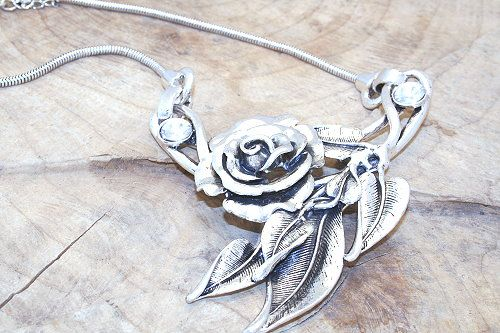 Chunky metal flower necklace with clear rhinestones.