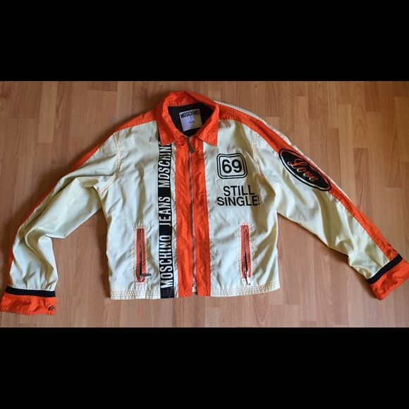 "Moschino Still Single on Bomber  jacket $1195-M Excellent condition Moschino Jeans bomber jacket. ""Love"" logo on sleeve, silver Moschino logo zipper pull, ""69"" & ""Still Single"" logos on chest. Whimsical & fun, this edgy jacket in cream & orange trim is rare & hard to find. Few pinhead sized spots on sleeve & one on collar. Lined w/mesh. Size tag was removed-see measurements. Size M/L Made in Italy. Retail $1195 nylon/cotton. 2 front zip pockets. Moschino Jeans printed on front of jacket…"