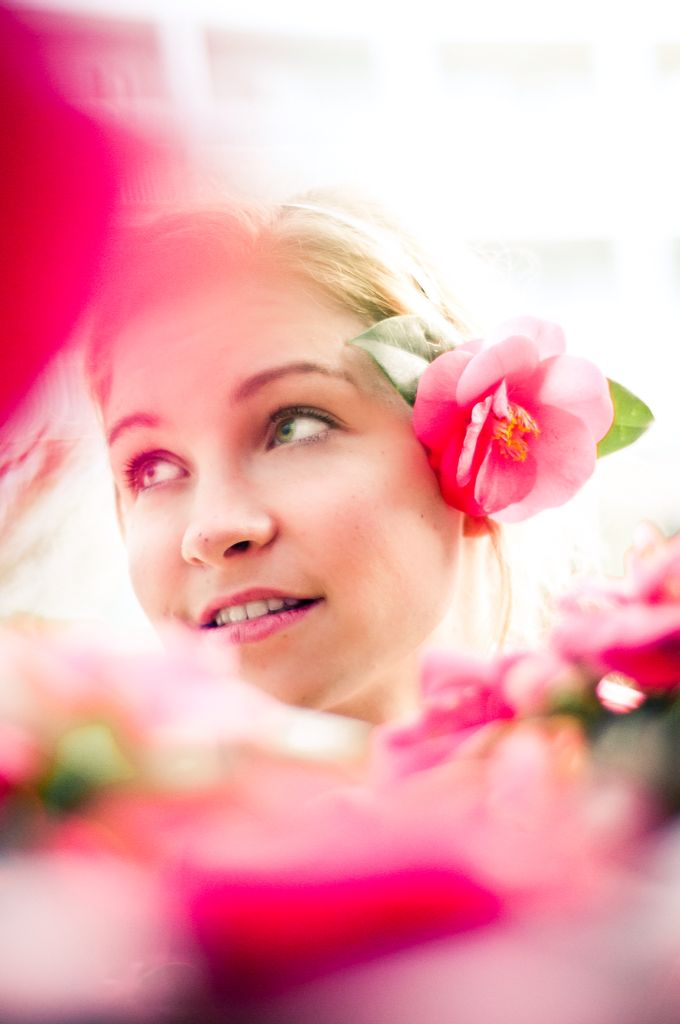 Photography portrait of woman in pink flowers in the sun summer