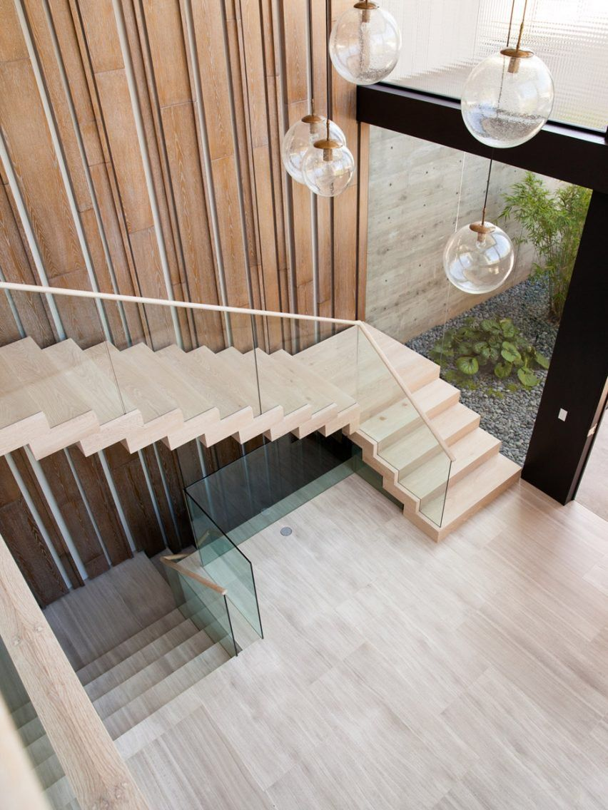 A Staircase Ascends To The Second Floor Along A Wall Clad With Backlit  Birch Wood
