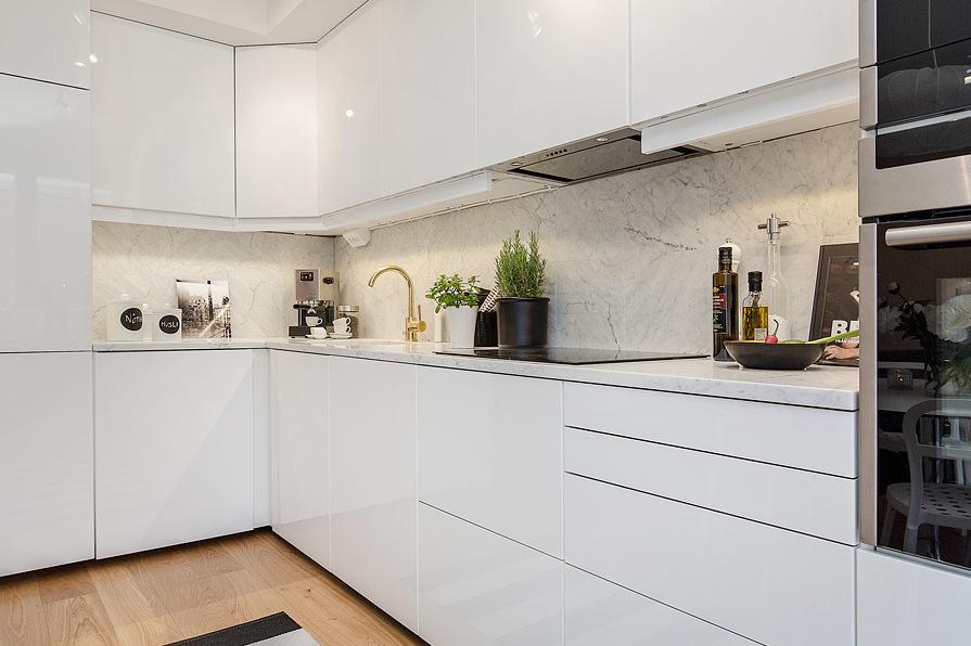 White kitchen Kivan yksinkertaiset kaapistot. Marmori välitilan seinässä ei nappaa.
