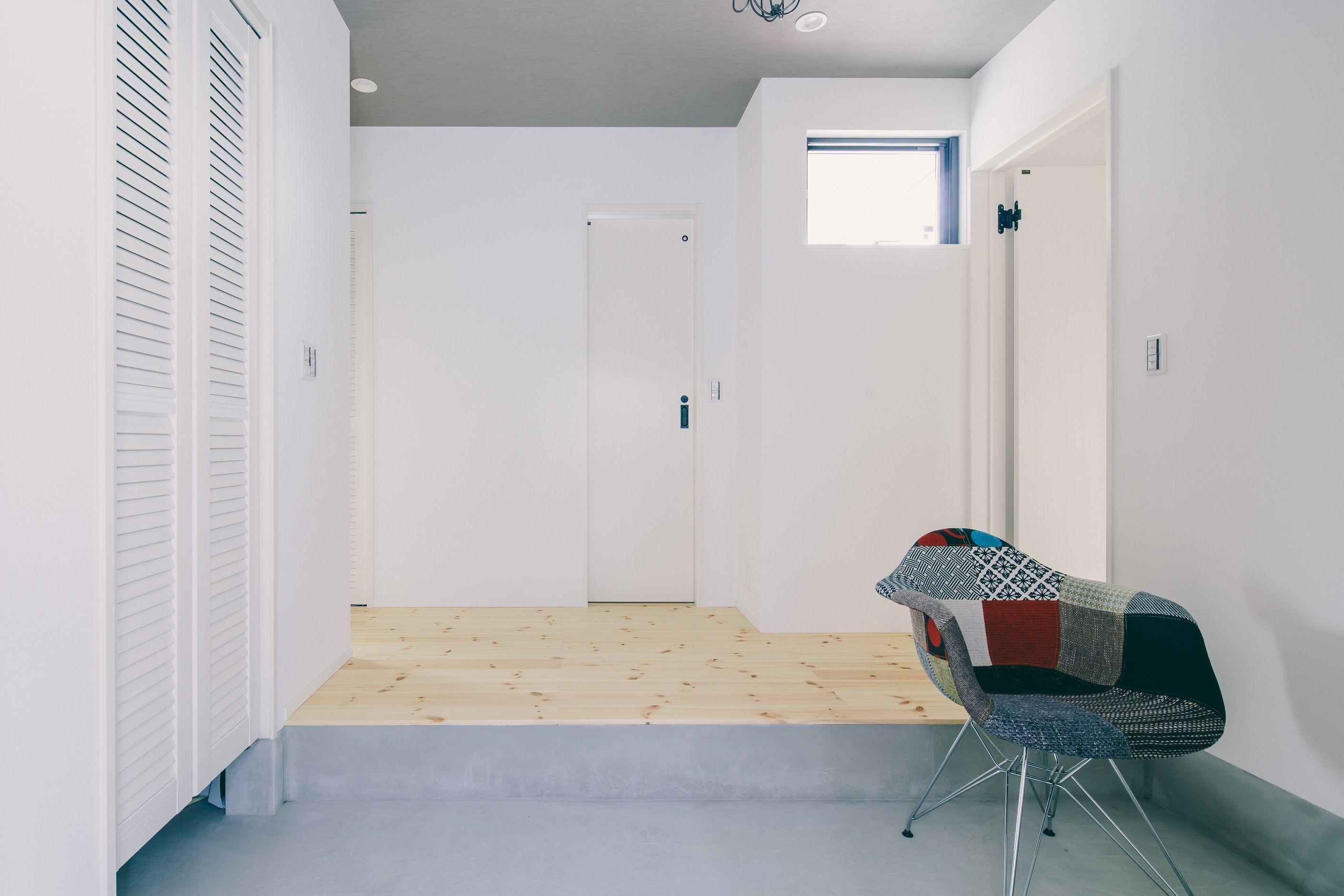 シンプルなインテリアに際立つおしゃれなチェアのある玄関 ルポハウス