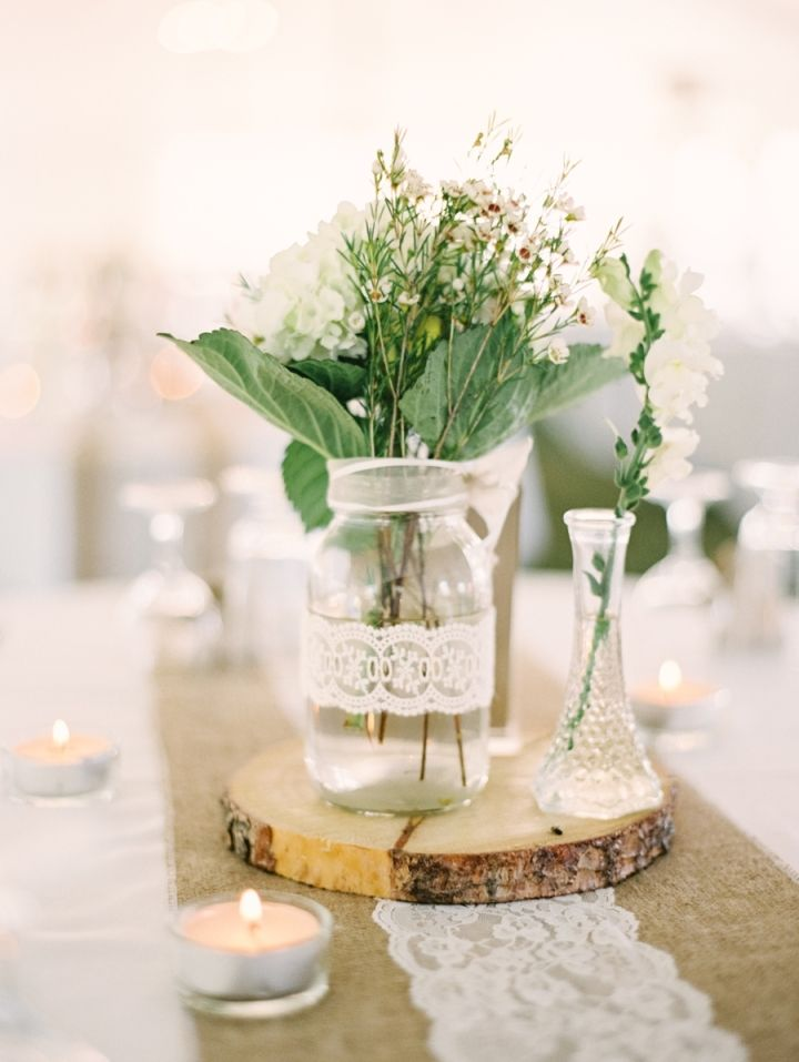 White flowers + green filled in mason jar + burlap + candles as wedding centrepiece #chicwedding #rusticchic #rusticelegance #rusticwedding #weddingcenterpieces