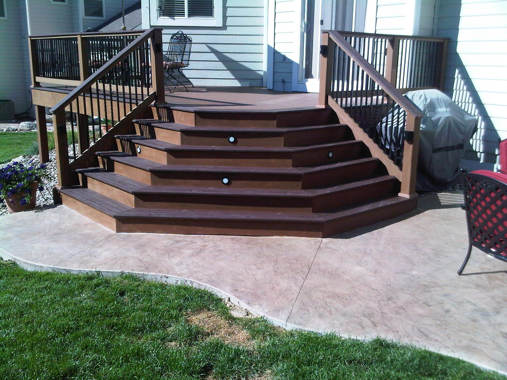Splayed TREX posite deck stairs onto Stamped concrete patio