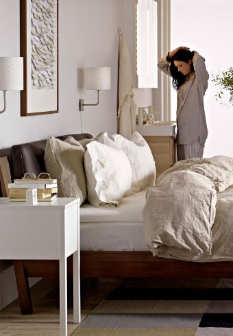femme dans une chambre avec lit fauteuil miroir tiroirs. Black Bedroom Furniture Sets. Home Design Ideas