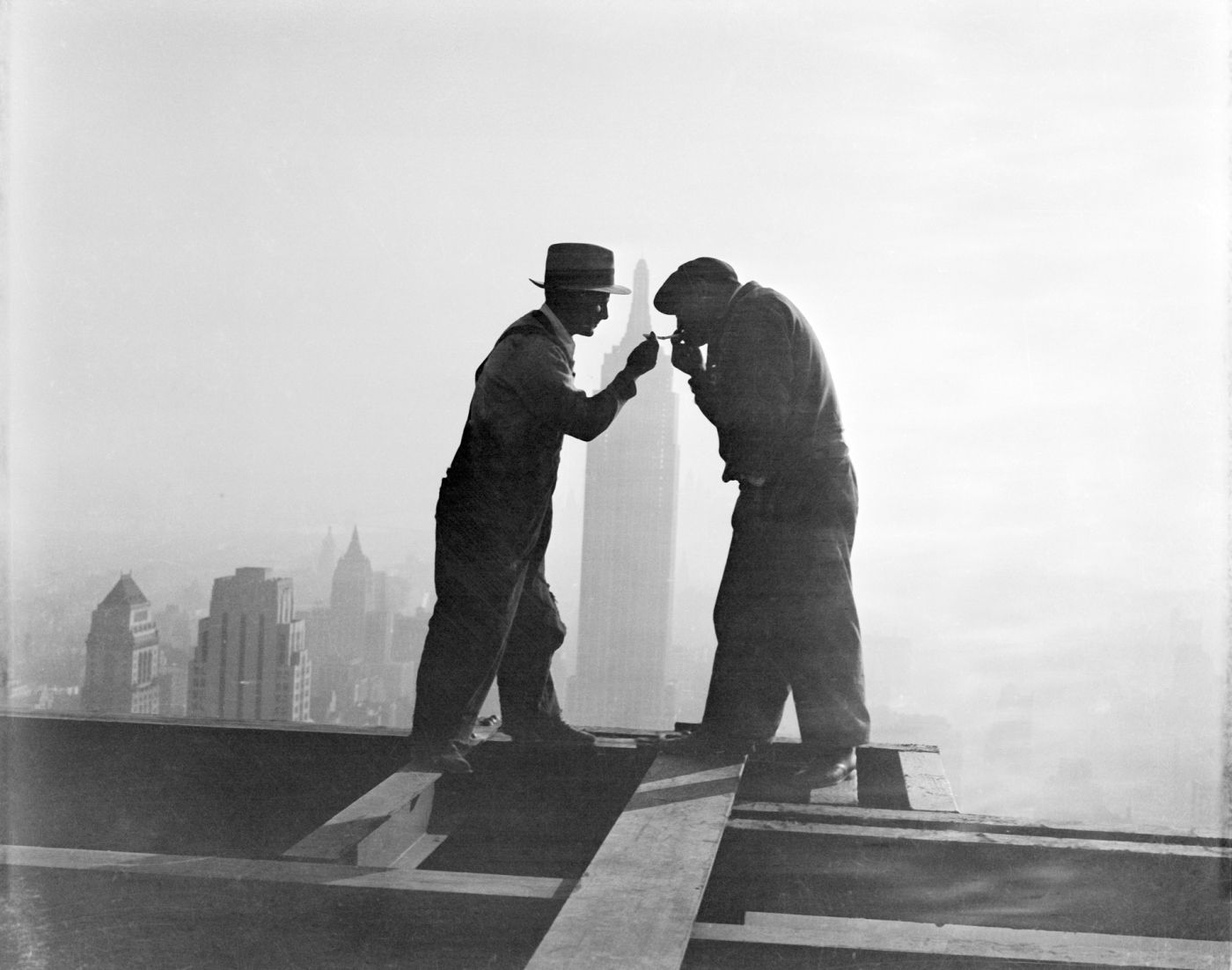 Two workmen share a cigarette atop the RCA Building in Rockefeller Center in front of the Empire State Building in New York City, on Dec. 2, 1932.
