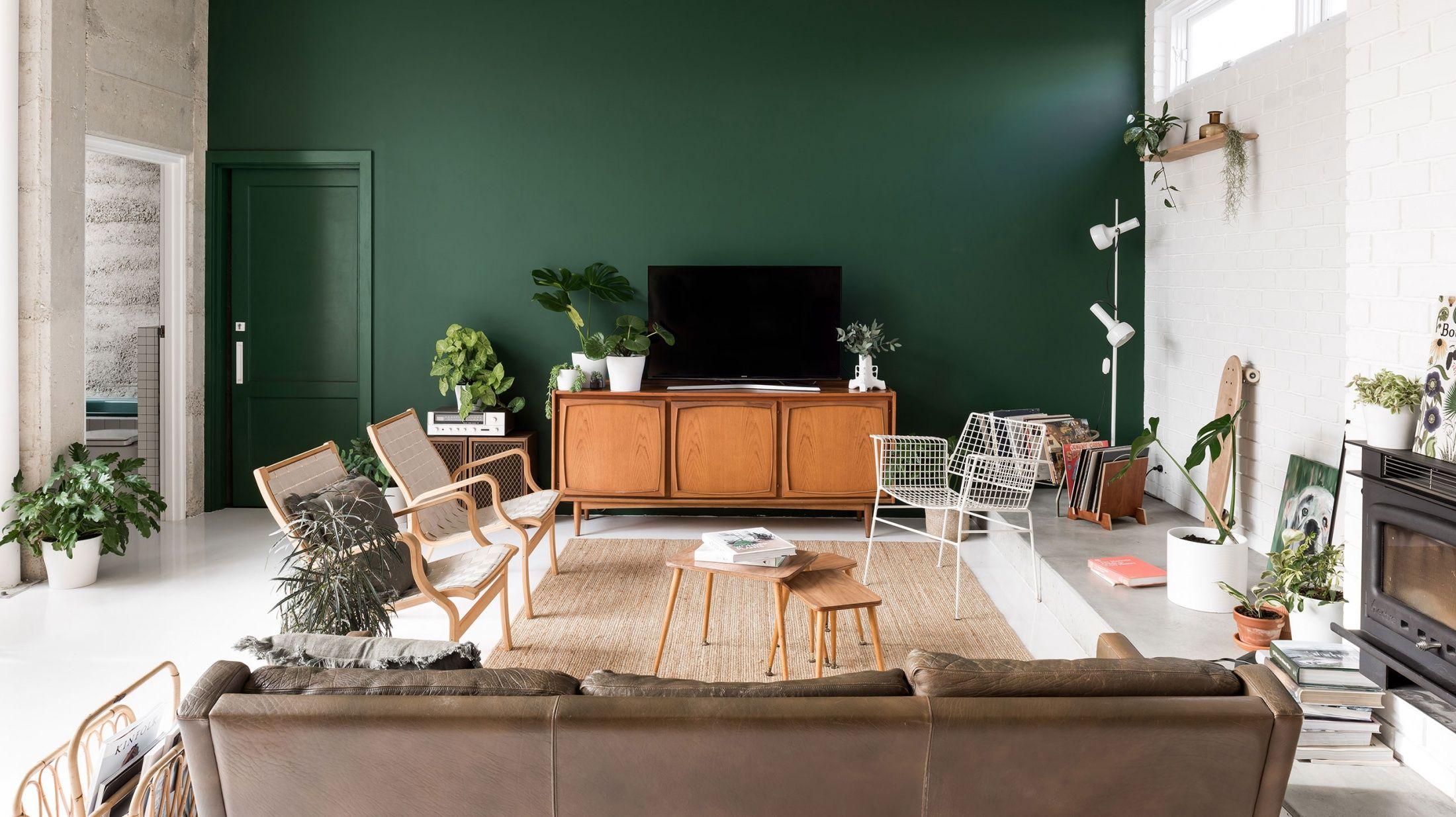 Dark green walls mcm plants white floors relaxed modern living room design