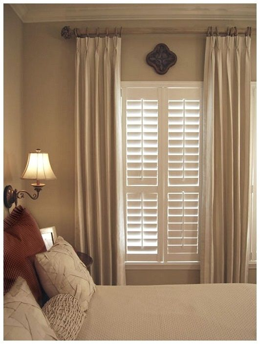 Beautiful wood blinds complemented with neutral drapes. A ...
