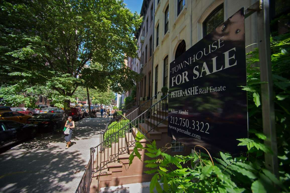 A pedestrian walks past a Peter Ashe Real Estate 'For Sale' sign displayed…