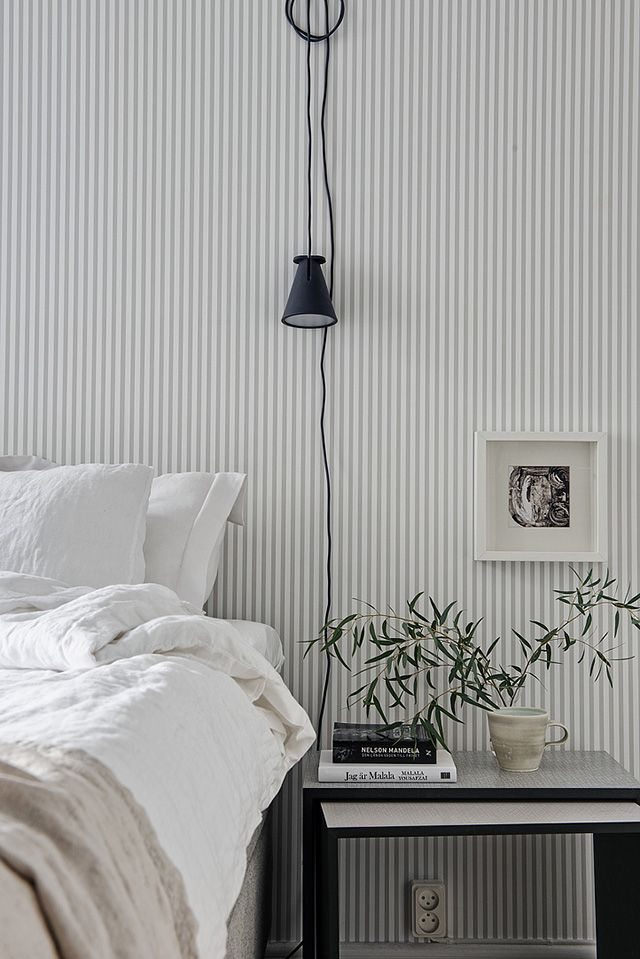 White Bedroom With A Hanging Lamp Simplistic Plant Night Stand Wallpaper Bedroom Striped Wallpaper Interior