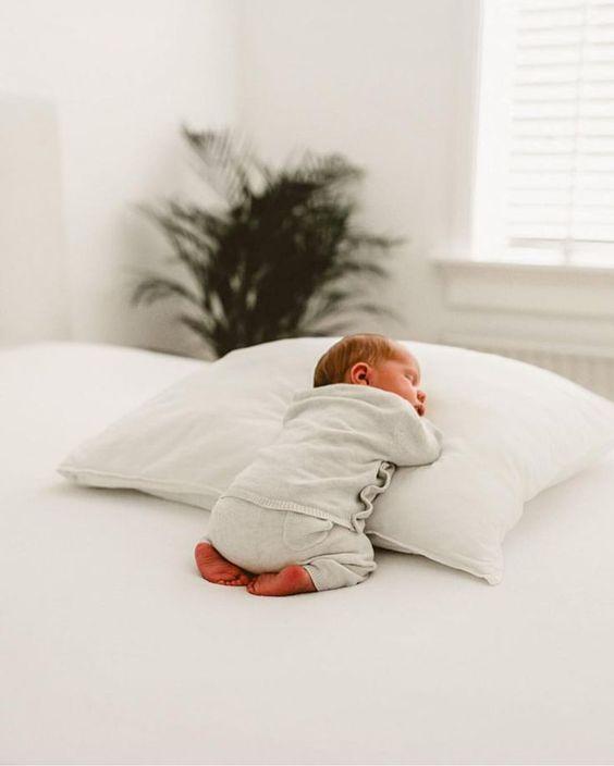 Kleines Wunder – Baby entspannt sich kuschelnd auf dem Bett.