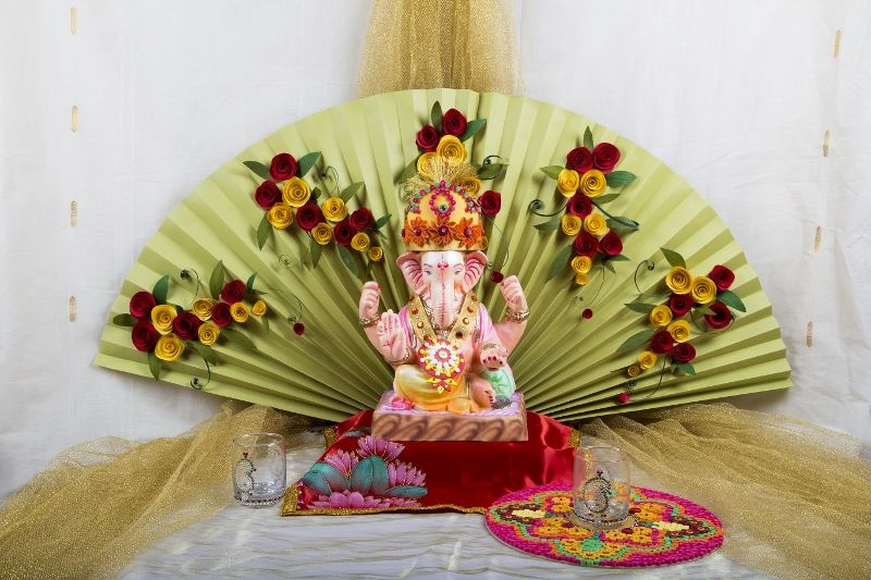 Fanfold decoration with paper flowers and ganpati in front for Artificial flower decoration for ganpati