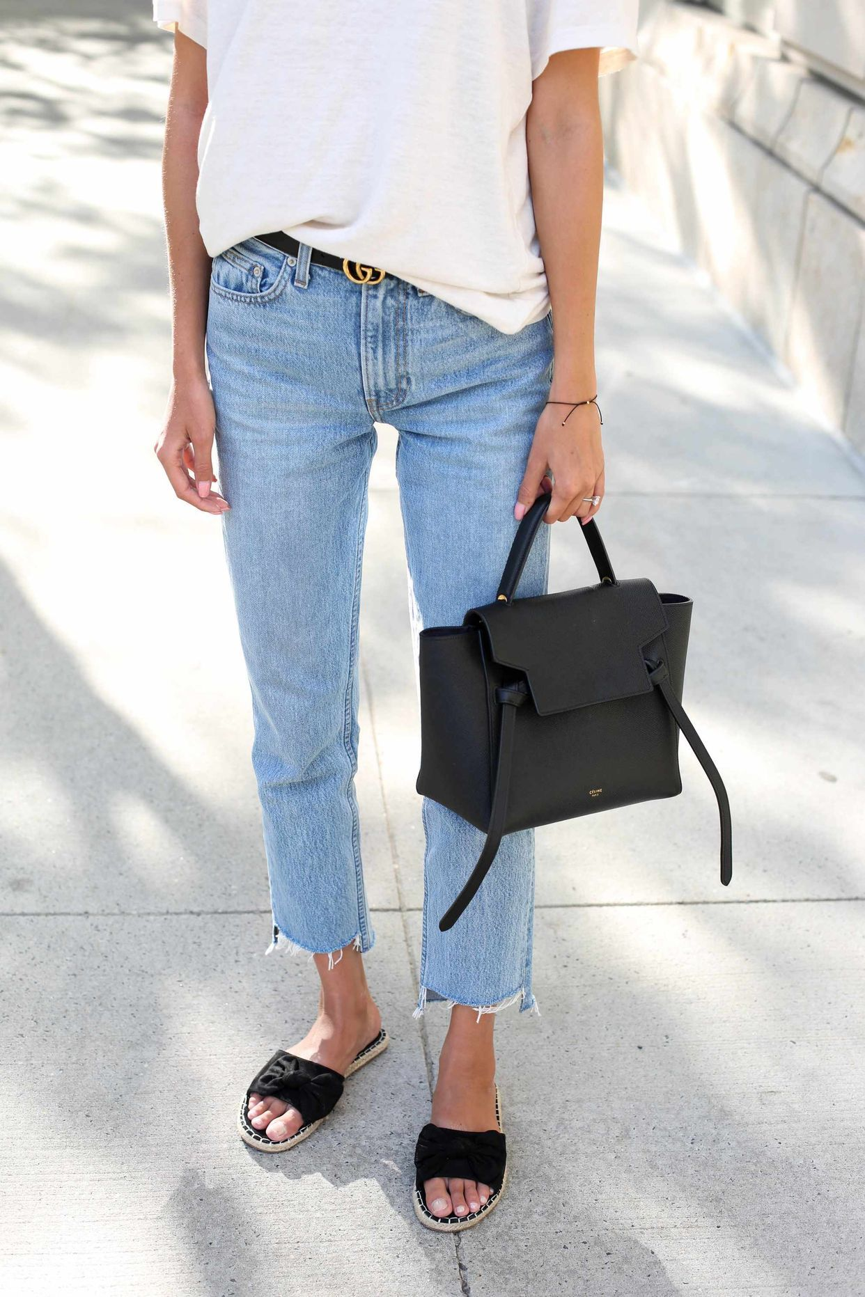 effortless cut off jeans, half tucked t-shirt, boxy handbag, black slide ons