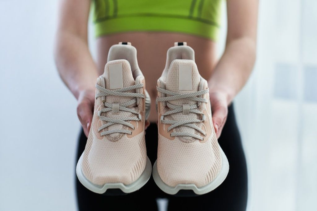 Fitness woman in sportswear holds sneakers for running. do sport and be fit. sports people with heal...