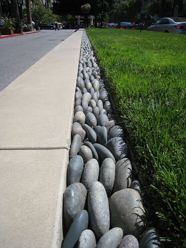River rock rain gutter this would be great around the for Landscape channel drain