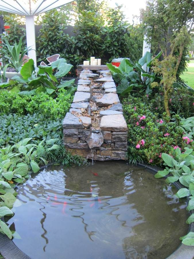 Very cool stone trough carries water to a small fish pond for Cool koi ponds