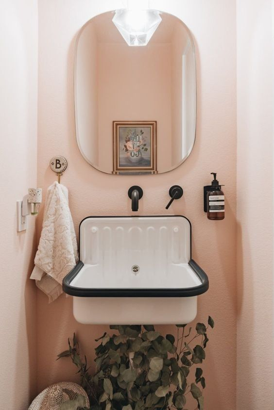 This townhome is a minimal, modern, monochromatic dream house with a pop of pink in its small bathroom. #housetour #hometour #pinkbathroom #bathroomideas #minimalisthome #smallbathrooms